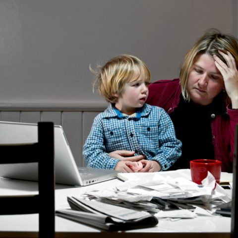 Woman and child having to make tough choices about what bills to pay. An example of those experiencing poverty.